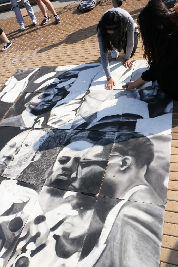students place drawings in a collection of drawings as part of a mosaic on the Einhorn Family Walk