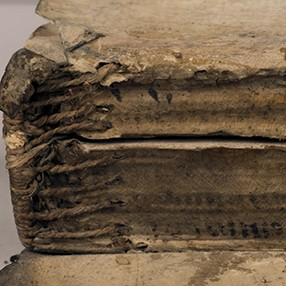 A detail of the sewn binding of an ancient book.
