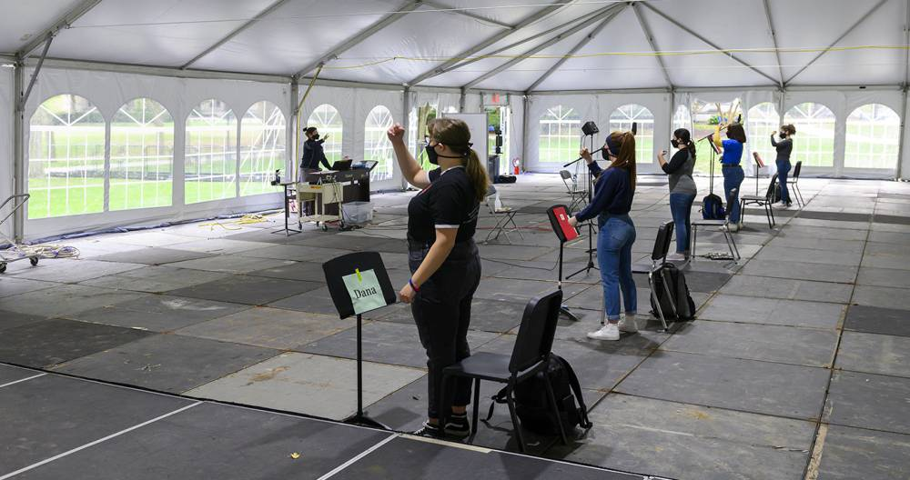 A woman in a face mask conducting to several students in face masks, inside a white tent