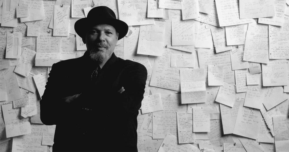 a black and white photo of Wilson standing in front of a wall covered in handwritten pages
