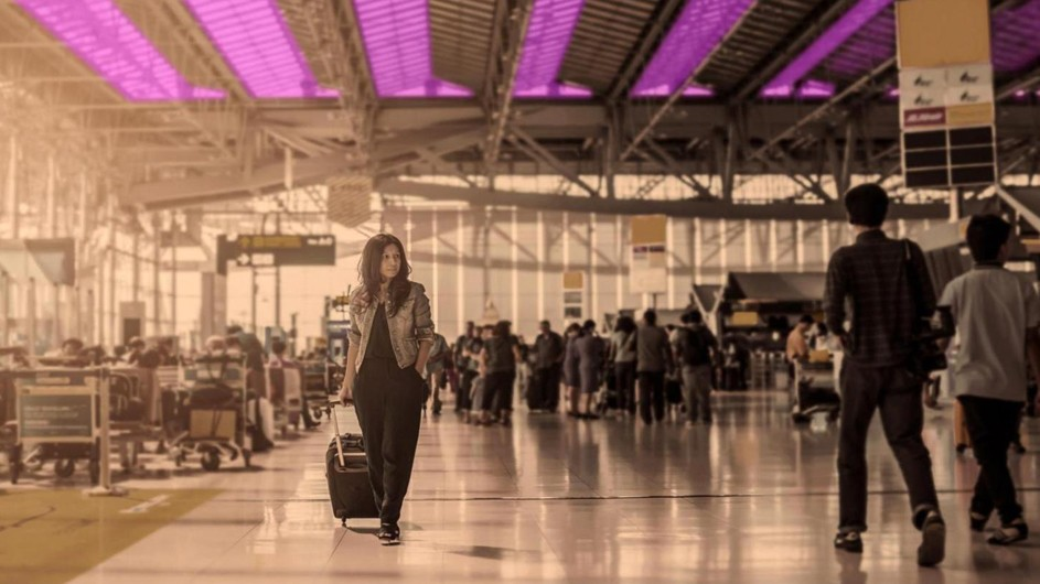 crowded airport terminal, woman with long brown hair, black dress, tan jacket walking under purple lamps, looking like vertical boards on ceiling