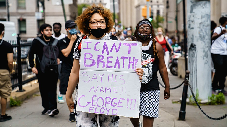 """A woman wearing a face covering, holding up a sign--which reads, """"I can't breathe! Say his name. George Floyd!!!--walking with a group of protestors.."""