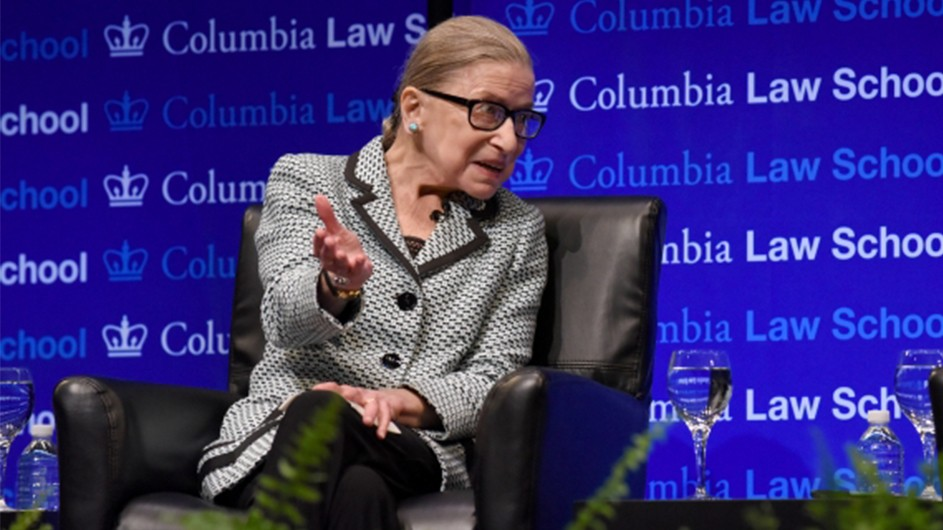 Justice Ruth Bader Ginsburg is seated in a black leather chair against a Columbia Law School backdrop, gesturing to a crowd of onlookers.