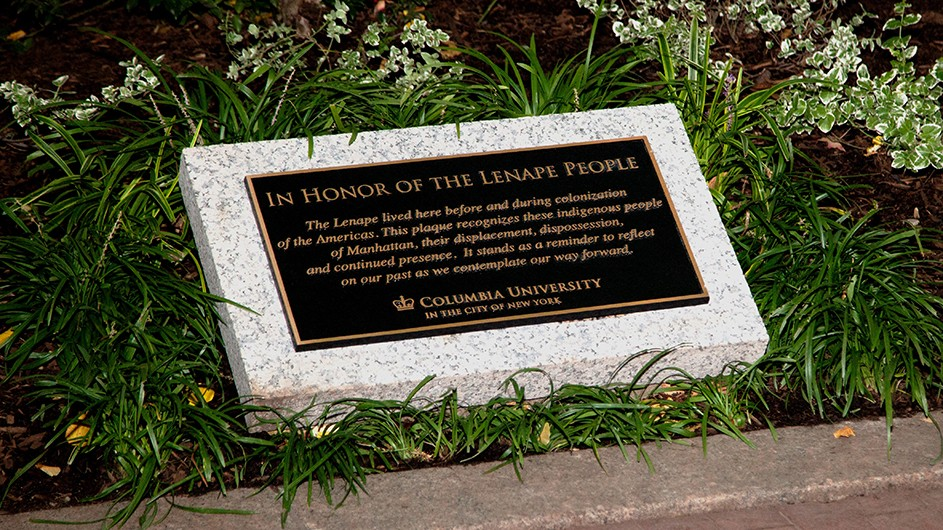 A black plaque with gold writing and gold trim on a stone displayed in a garden at Columbia University honoring the Lenape People