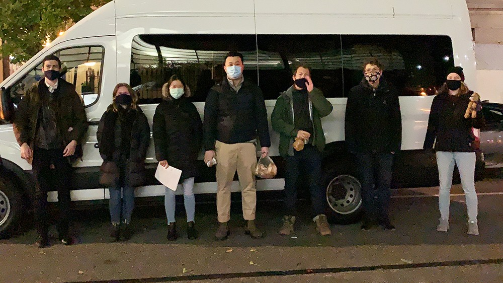 A photo of seven people wearing masks standing in front a white van on the street at night.