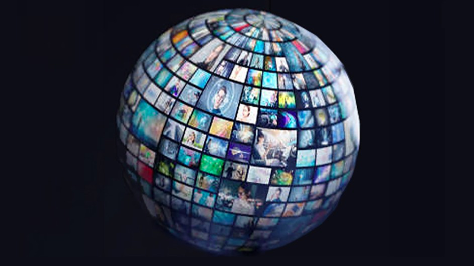 A globe with photos of people all over it, against a black backdrop