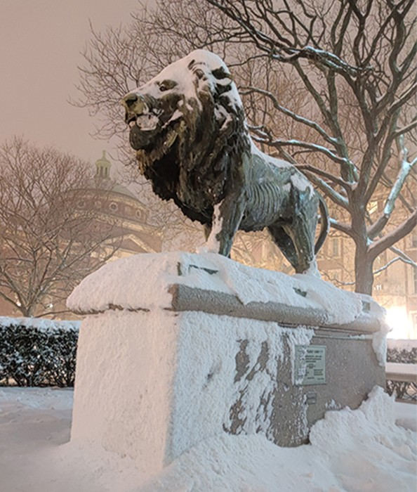 A grey statue of a lion on a stone pedestal is enshrouded in a blanket of snow.