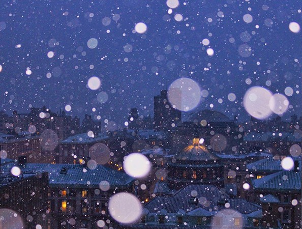 Enlarged snowflakes refract upon a blue sky background looking out over Morningside campus' domed Low library and other buildings.