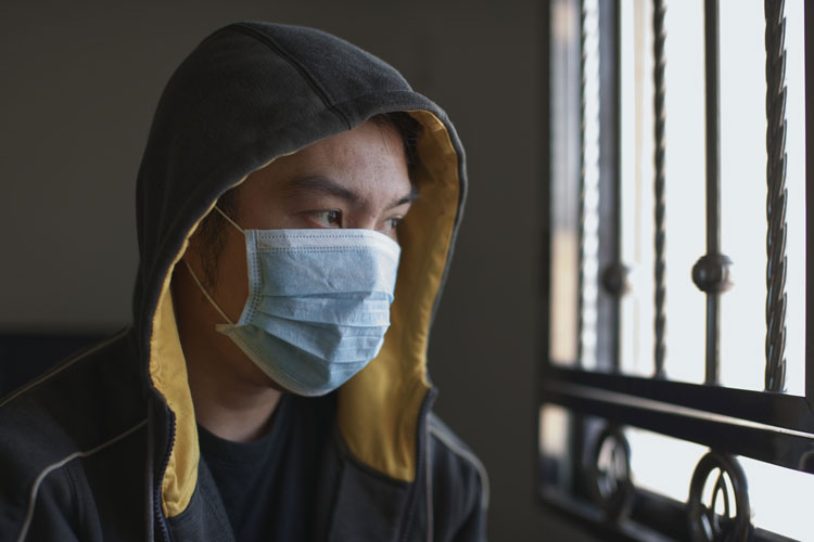 Young man wearing a mask and staring out of a window.