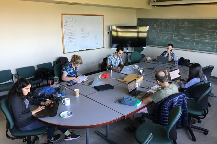6 members of the Steamboat Geyser team arrayed around a table with their computers