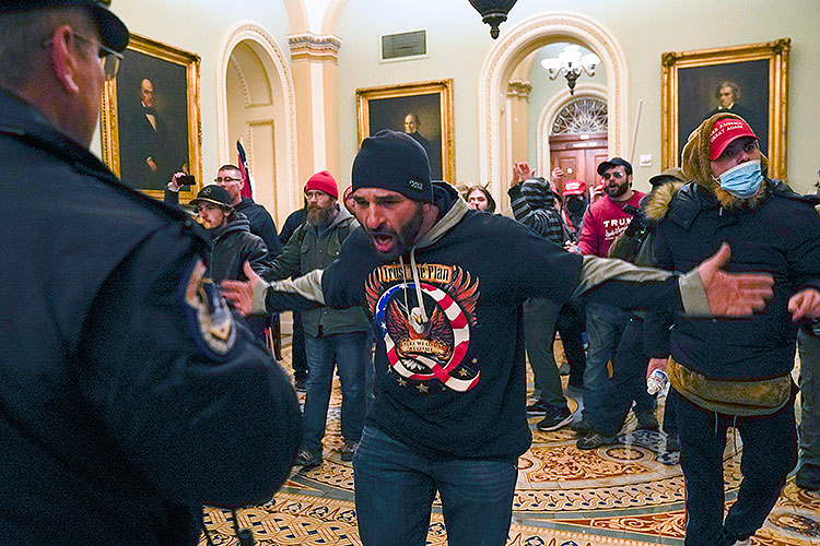 One of the militants who broke into the US Capitol gestures toward police officer