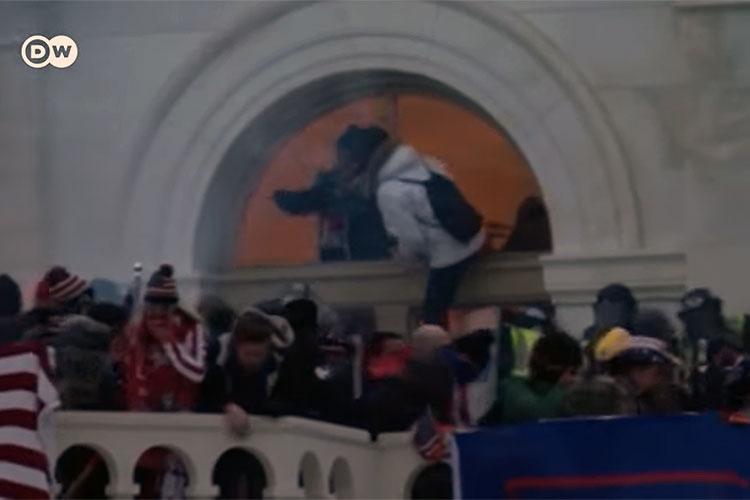 Rioters entering the U.S. Capitol through a broken window