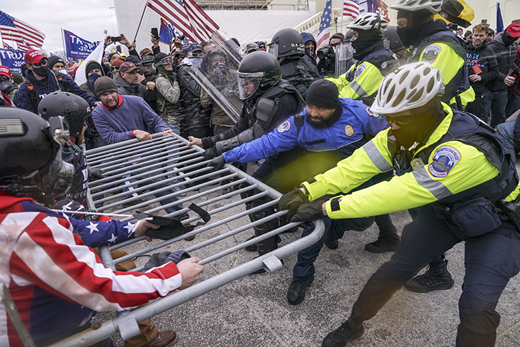 Trump supporters try to break through a police barrier while officers hold onto the barrier and pull it back