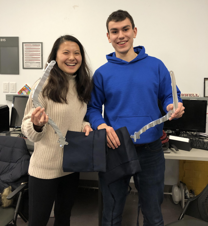 Two students hold a robotic arm