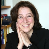 Anya Schiffrin, a woman with brown hair, in a black blazer with her hands clasped by her face, smiling.