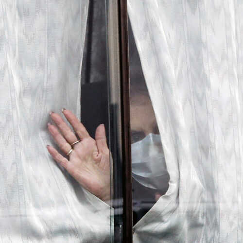 A woman waves from a window.