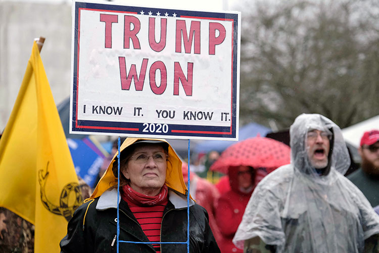 """Woman holds protest sign proclaiming Donald Trump's 2020 victory, months after he lost the election. The signs reads """"Trump Won. I know It. You know it."""""""